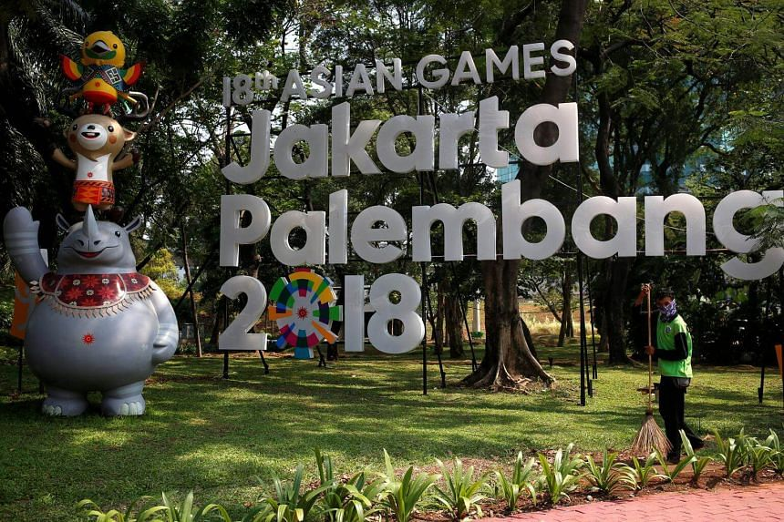 A worker cleans near a sign for the upcoming 2018 Asian Games, which would be held in both Jakarta and Palembang, on Sept 17, 2017.