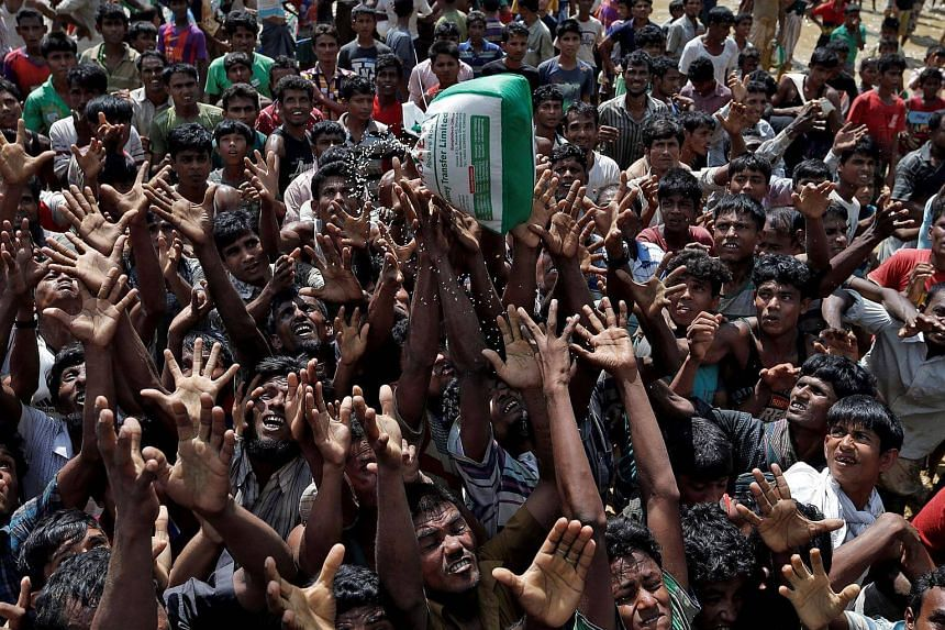Rohingya refugees react as aid is distributed in Cox's Bazar, Bangladesh, on Sept 21, 2017.