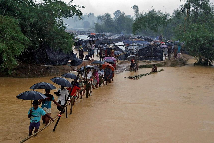 People crossing a river from a Rohingya refugee camp in Cox's Bazar, Bangladesh, on Sept 19, 2017.