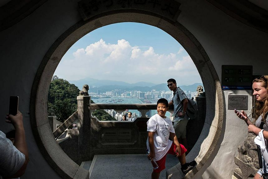 Tourists pose for a photograph at Victoria Peak in Hong Kong, China.