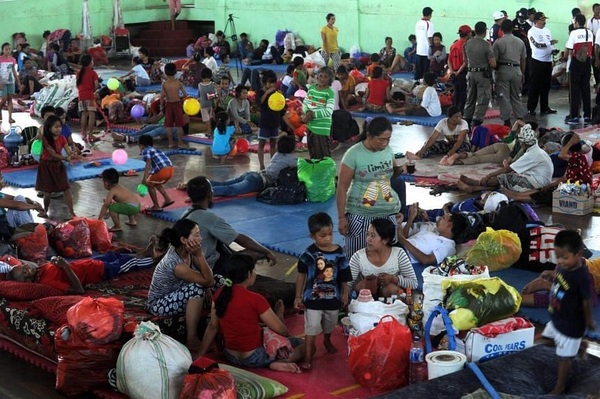 Villagers rest after being evacuated during the raised alert levels for the volcano on Mount Agung in Klungkung regency on the Indonesian resort island of Bali on Sept 22, 2017.
