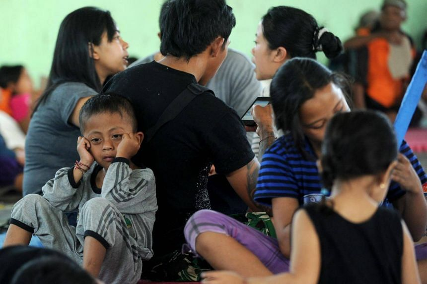 A boy sits behind his parents and villagers after being evacuated during the raised alert levels for the volcano on Mount Agung in Klungkung regency on the Indonesian resort island of Bali on Sept 22, 2017.
