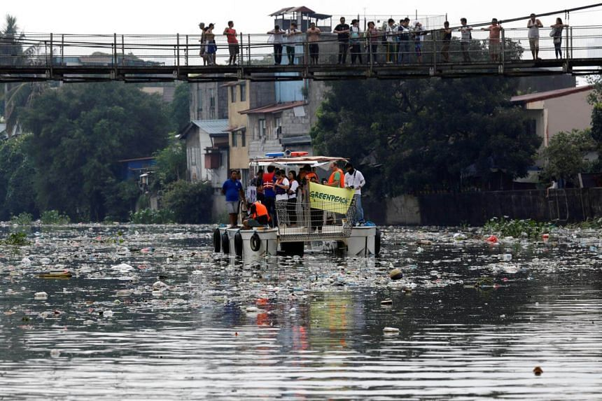 Local residents look on as a team from the governmental Pasig River Rehabilitation Commission and Greenpeace activists inspect the polluted Pasig River in San Juan, Metro Manila, Philippines on Sept 8, 2017.
