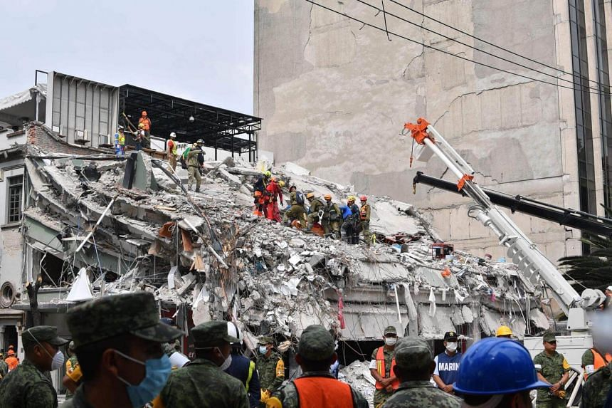Rescuers remove the body of a man who survived the quake but died before they were able to reach him during the search for survivors at a flattened building in Mexico City on Sept 21, 2017.