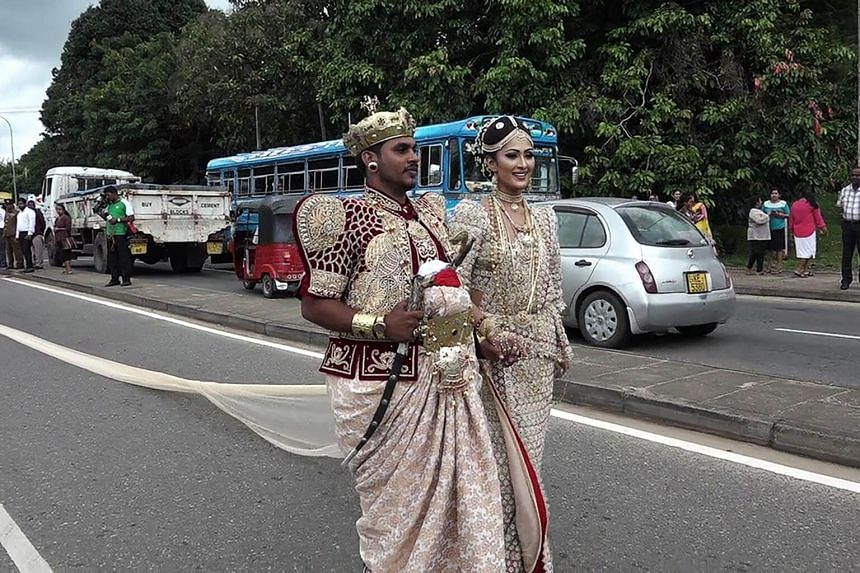A Sri Lankan wedding couple walk along a road as as a bride attempts to set a record for the longest wedding saree, with a length of 3.2 kms (two-miles), in the central district of Kandy on Sept 22, 2017.
