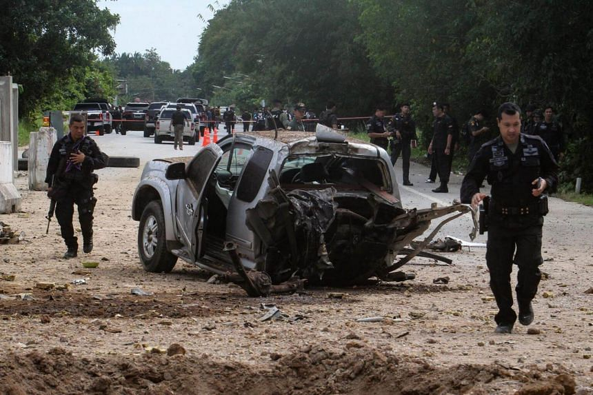 Thai army rangers walk through the scene of a roadside bomb which killed four army rangers in the restive Southern Thai province of Pattani on Sept 22, 2017.