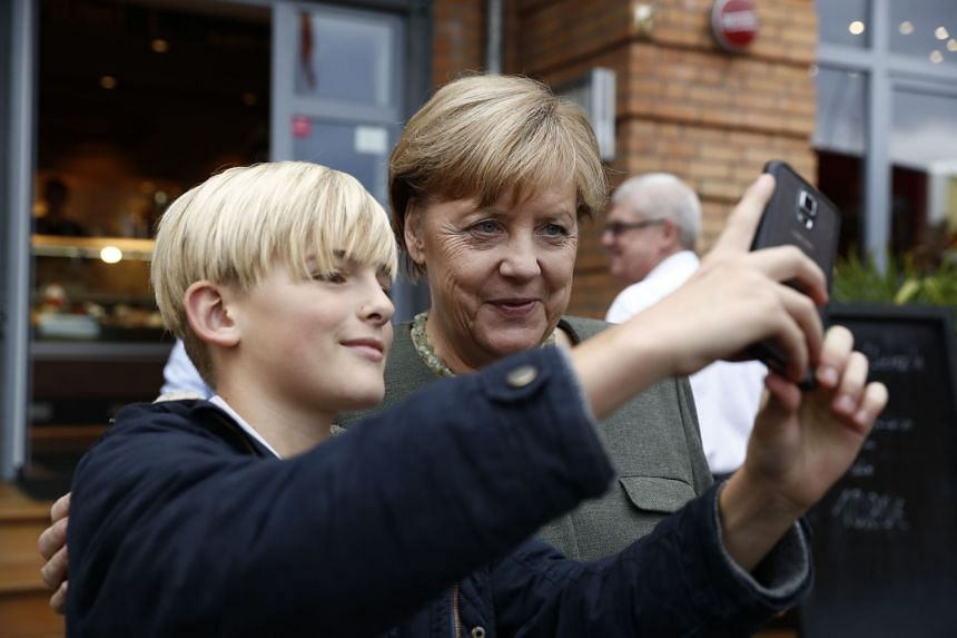 Angela Merkel poses for a selfie with a boy before addressing an election campaign rally.