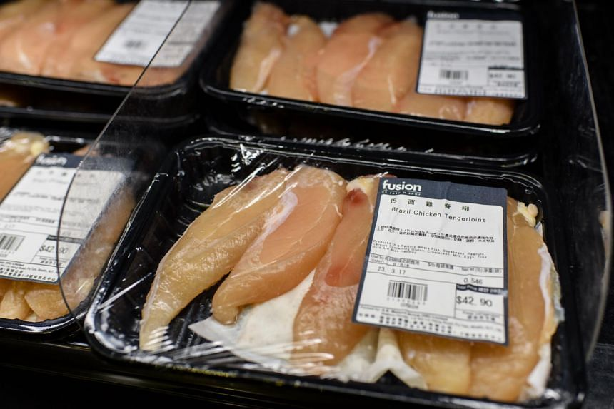 Packs of previously frozen Brazil chicken legs are seen stacked on a trolley shortly after a member of staff cleared them from the shelves of a supermarket in Hong Kong, on March 21, 2017.