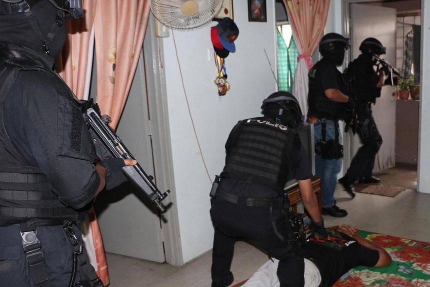 A suspected Abu Sayyaf Group militant being held down while armed counter-terrorism officers combed the premises. Seven Filipino suspects were detained in the latest round of raids in Kuala Lumpur on Sept 14.COUNTER-TERRORISM DIVISION