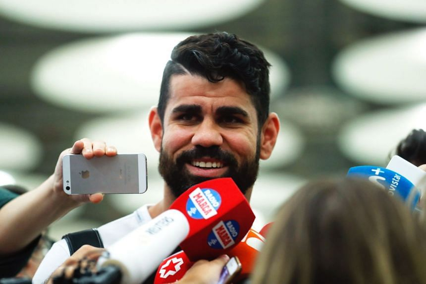 Spanish striker Diego Costa talks to journalists upon his arrival in Madrid.