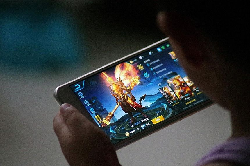 """Tencent's Honour Of Kings has 200 million registered users in China alone. But it has been denounced as """"poisonous"""" by Beijing after a teenager had a stroke after playing the game non-stop for 40 hours. A customer using a smartphone in front of the l"""