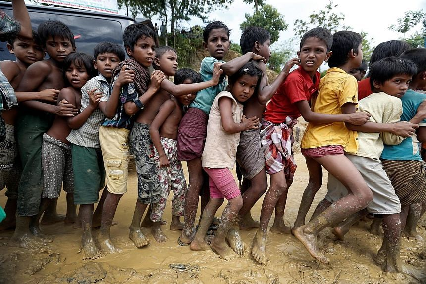 """Rohingya refugee children queueing for aid in Cox's Bazar, Bangladesh, on Thursday. Doctors Without Borders has warned that the country's refugee camps are on the brink of a """"public health disaster""""."""