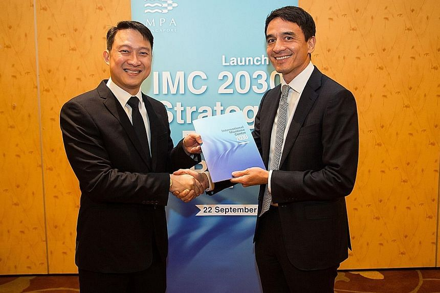 Senior Minister of State for Transport Lam Pin Min receiving a copy of the International Maritime Centre 2030 Advisory Committee's report from committee chairman Andreas Sohmen-Pao at Marina Bay Sands.