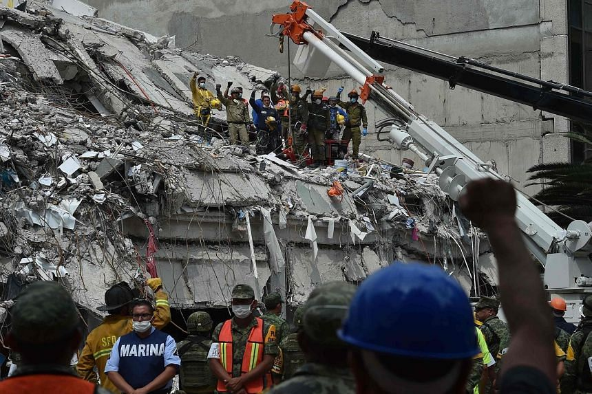 Rescuers and firefighters raising their fists to pay their respects to a man who survived the quake but died before they could reach him during their search for survivors at a flattened building in Mexico City on Thursday.
