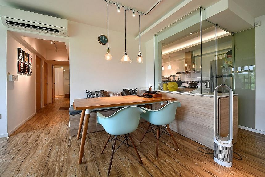 Ms Jessica Koh's (left, with her mother Sally Tan) five-room HDB flat has plenty of wooden surfaces and a glass-enclosed kitchen, while pop art representations of cultural icons, such as Katy Perry, Rihanna and Taylor Swift, lend a funky touch.