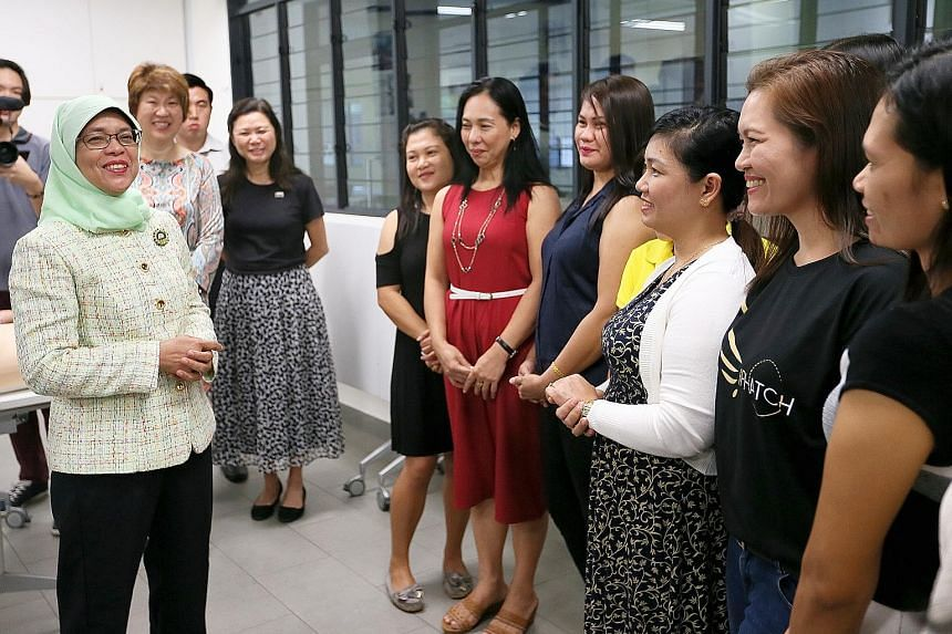President Halimah Yacob chatting with a group of foreign domestic workers at Agape Village yesterday. She also dropped in at the Mamre Oaks day activity centre for adults with intellectual disabilities.
