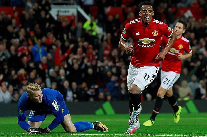 Forward Anthony Martial wheeling away in delight after scoring Manchester United's fourth goal against Burton in the League Cup on Wednesday. He will hope to be in the starting XI today.