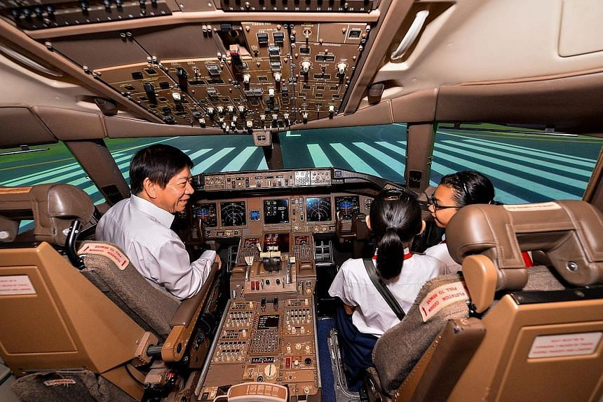 Transport Minister Khaw Boon Wan in a Boeing-777 flight simulator with beneficiaries of the Community Chest, who were given a tour of the SIA Training Centre in Changi yesterday. The Ministry of Transport and its statutory boards raised $1 million fo