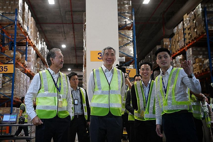Prime Minister Lee Hsien Loong touring logistics giant YCH's flagship headquarters, Supply Chain City, in Jurong West yesterday with (from left) YCH chairman Robert Yap; head of operations innovation Khoo Ngiap Seng; and Mr Ngoh Jun Dat, who is with