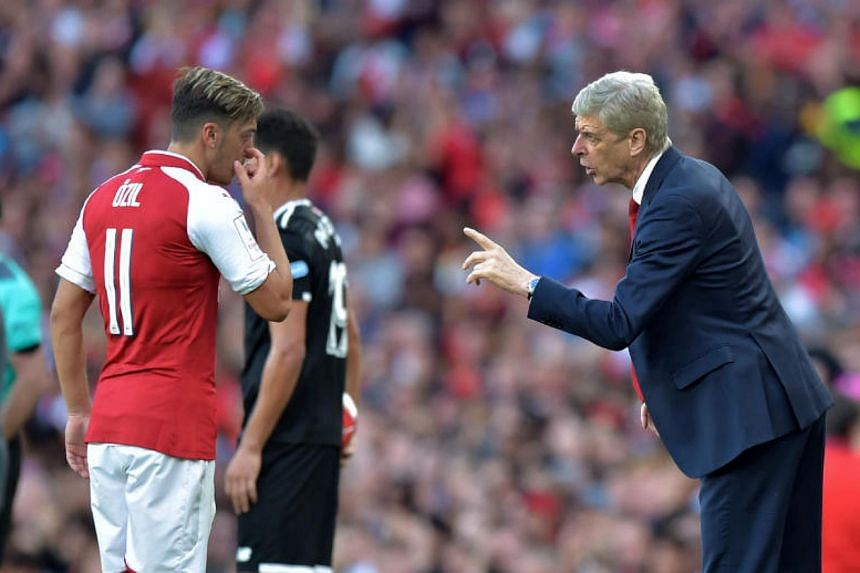 Arsenal's French manager Arsene Wenger instructing German midfielder Mesut Ozil during the pre-season friendly football match against Sevilla at The Emirates Stadium in north London on July 30, 2017.
