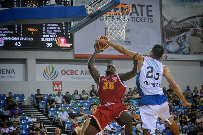 Ryan Wright (left) of the Singapore Slingers tries for a shot as Zhang Zhaoxu of the Shanghai Sharks blocks him during the Merlion Cup semi-final at the OCBC Arena on Sept 23, 2017.