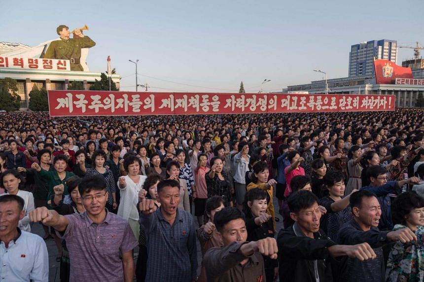 Participants of a mass rally shout slogans as they gather before a banner reading 'let us beat down the sanctions of the imperialists with great progress of self-reliance' on Kim Il-Sung sqaure in Pyongyang on Sept 23, 2017.