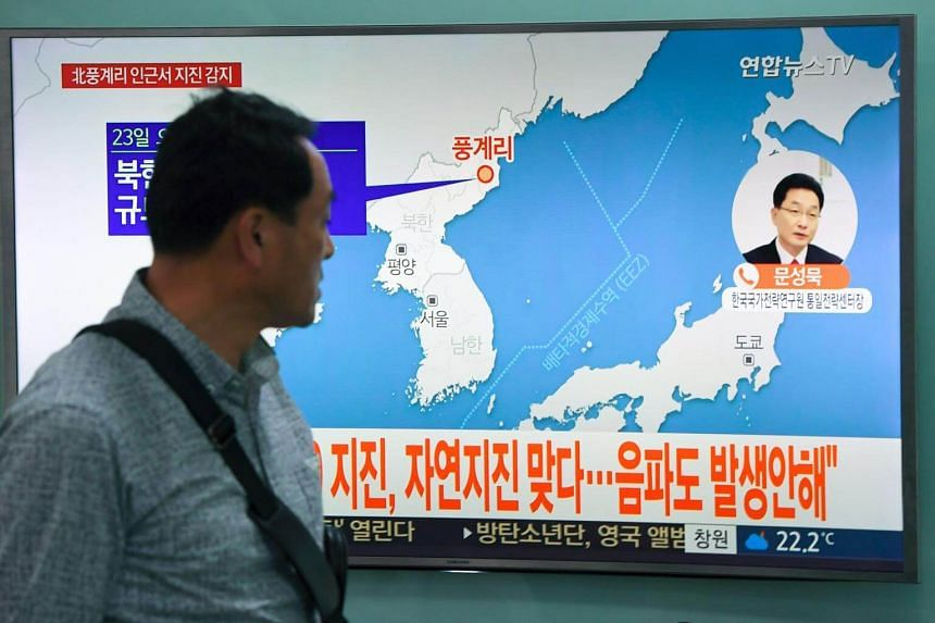 A man watches a television news screen showing a map of the epicenter of an earthquake in North Korea, at a railway station in Seoul on Sept 23, 2017.