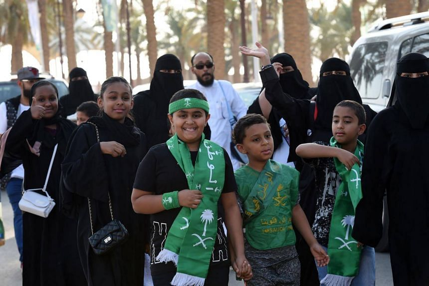 Saudi families arrive outside a stadium to attend an event in the capital Riyadh on Sept 23, 2017 commemorating the 87th anniversary of the founding of Saudi Arabia.