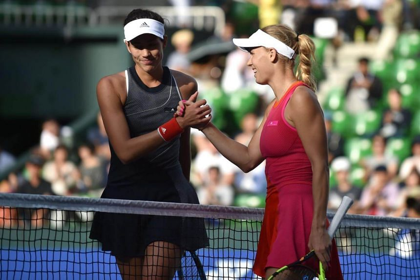 Caroline Wozniacki of Denmark (right) shakes hands with Garbine Muguruza of Spain after victory during their women's singles semi-final match at the Pan Pacific Open tennis tournament in Tokyo on Sept 23, 2017.
