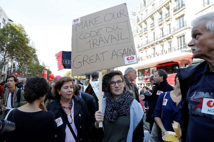 "A woman holds a placard reading ""Make our labour laws great again"" during a rally to protest the French government's proposed reforms in labour laws, in Paris, on Sept 21, 2017."
