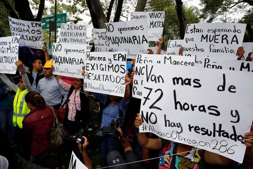 People hold posters during a protest against the lack of results in the rescue operations for their loved ones along a street next to a collapsed building after an earthquake in Mexico City, Mexico, on Sept 22, 2017.