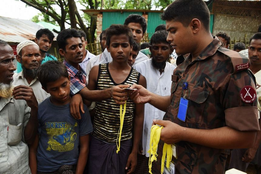 Rohingya refugees receiving new ID card from a soldier at the entrance of the Bangladeshi government registration office at the refugee camp of Kutupalong near in Ukhia, on Sept 22, 2017.
