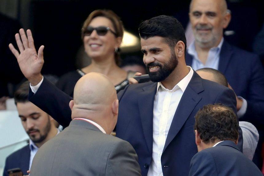 Costa (centre) attends the La Liga match between Atletico Madrid and Sevilla.
