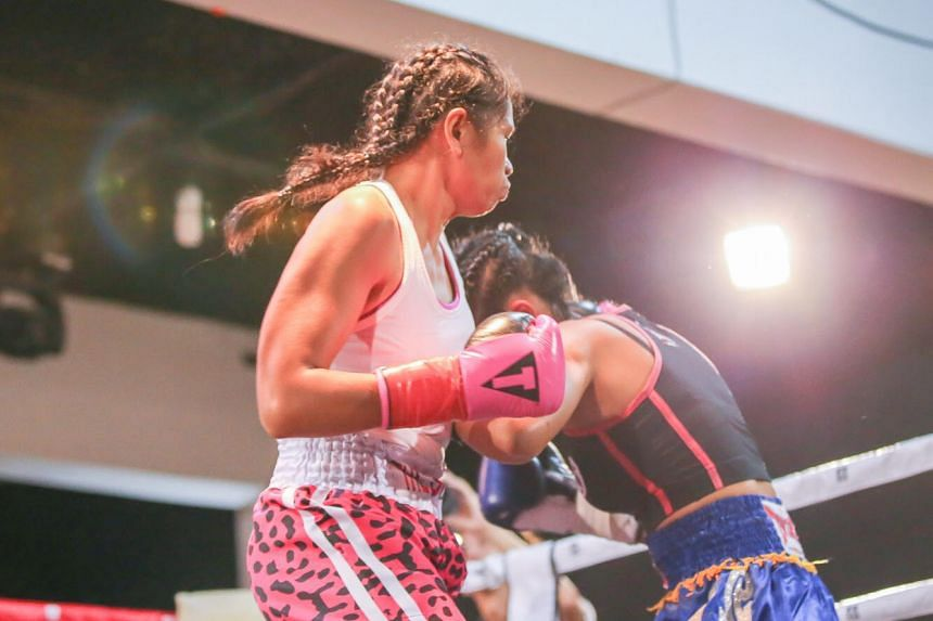 Singapore boxer Nurshahidah Roslie (left) claimed two titles after she executed a third-round technical knockout of Thailand's Siriphon Chanbuala.
