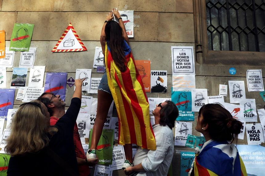 A woman wearing an Estelada (Catalan separatist flag) pastes posters on the wall in support of the banned Oct 1st independence referendum in Barcelona, Spain, on Sept 24, 2017.