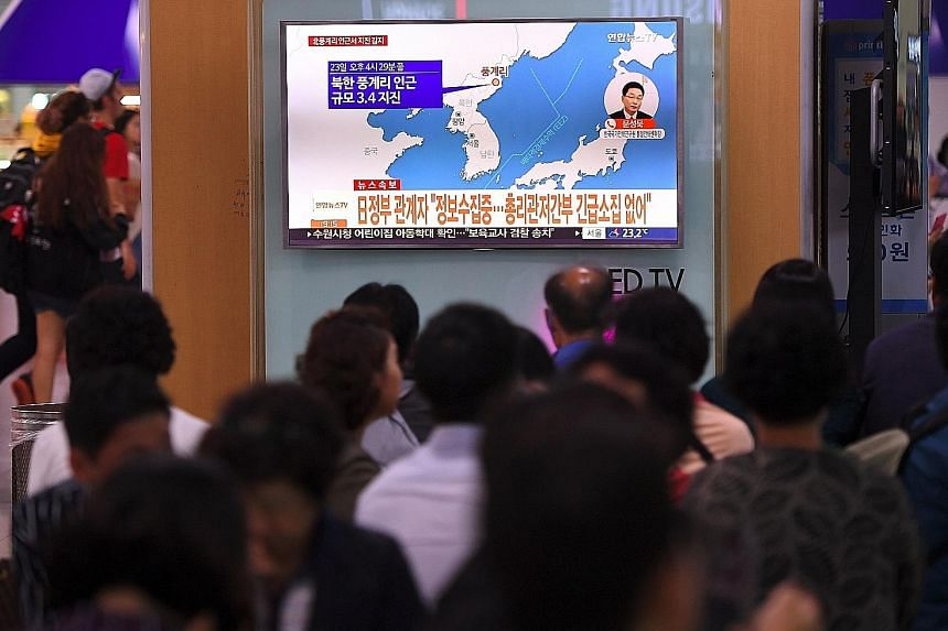 People crowding around a TV screen showing the epicentre of the quake at a railway station in Seoul yesterday. News of the quake coincided with Iran's announcement of its successful test of a new medium-range missile.
