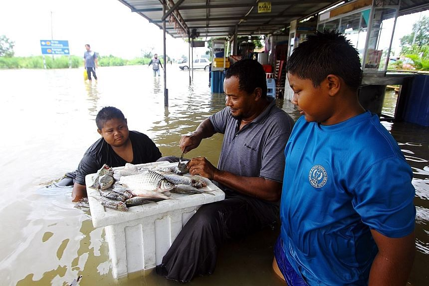 Mr Norzamlan Abu Seman, 30, with some of the 10kg of fish he caught when rain water submerged a road in Taman Seri Lancang Mata Ayer in Perlis. A total of 1,672 people were evacuated in the state.