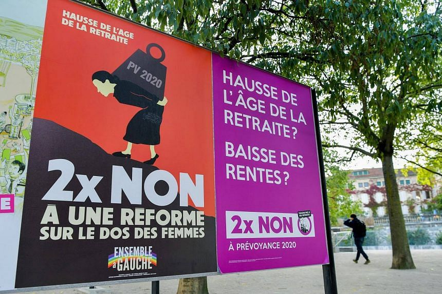 A person passes an electoral poster concerning a nation wide vote on pension in Lausanne, Switzerland on Sept 23, 2017.
