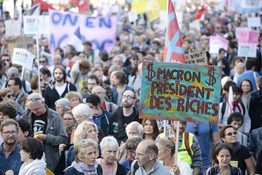 """A protester holds a sign reading """"Macron president of rich people"""" in Paris."""