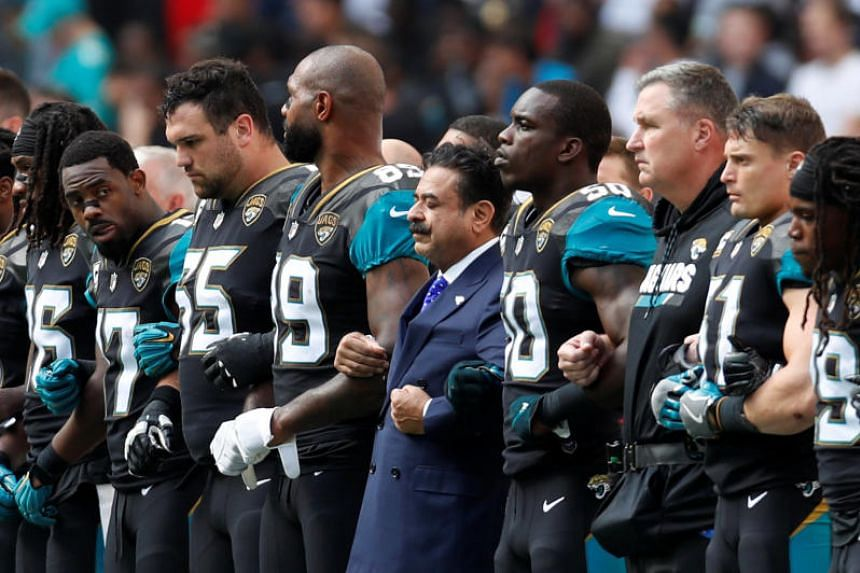 Jacksonville Jaguars owner Shahid Khan links arms with players during the national anthem before the match  at London's Wembley stadium on Sept 24, 2017.