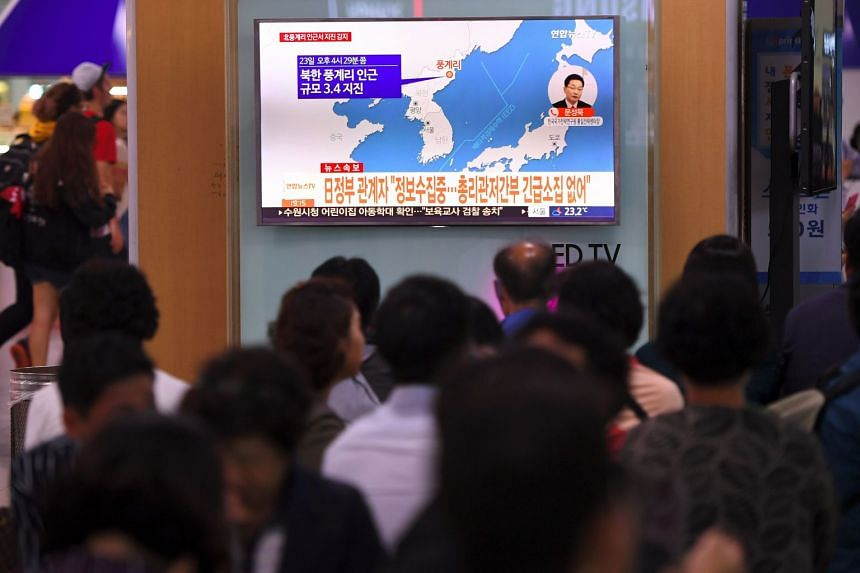 People in Seoul watch a TV news screen showing a map of the quake's epicentre.