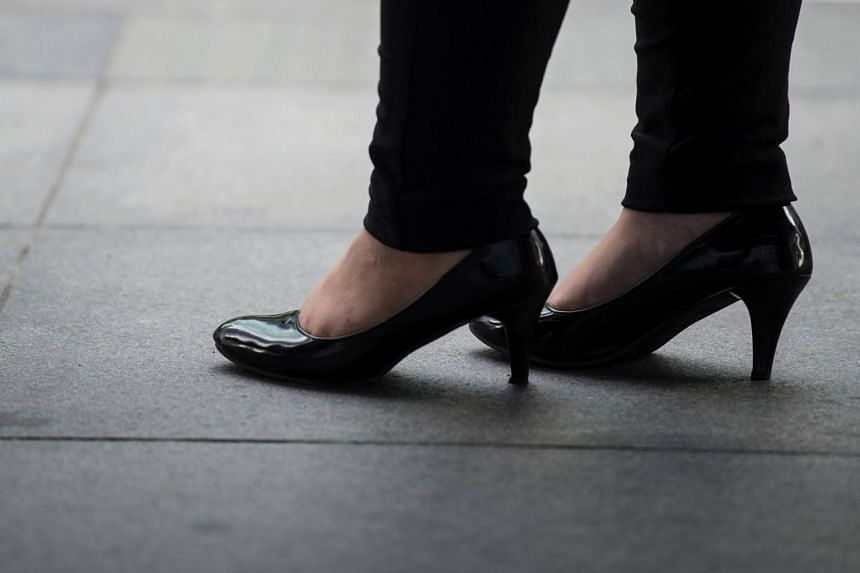 An office worker is seen wearing high-heeled shoes in Makati, Manila's financial district, on Sept 25, 2017.