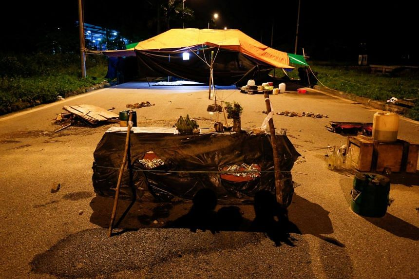 A coffin and petrol bottles are seen near protesting camp sets by villagers to block entrance of Hong Kong's Pacific Crystal textiles factory in HaiDuong province, Vietnam on July 13, 2017.