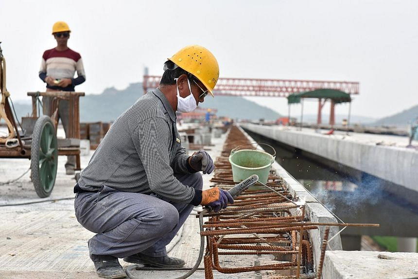 A worker welding reinforcement bars at a construction site in Hefei. While UBS sees S&P's downgrade of China's credit rating as no cause for panic, IG Asia market strategist Pan Jingyi feels that the coming Golden Week break may make the market excep