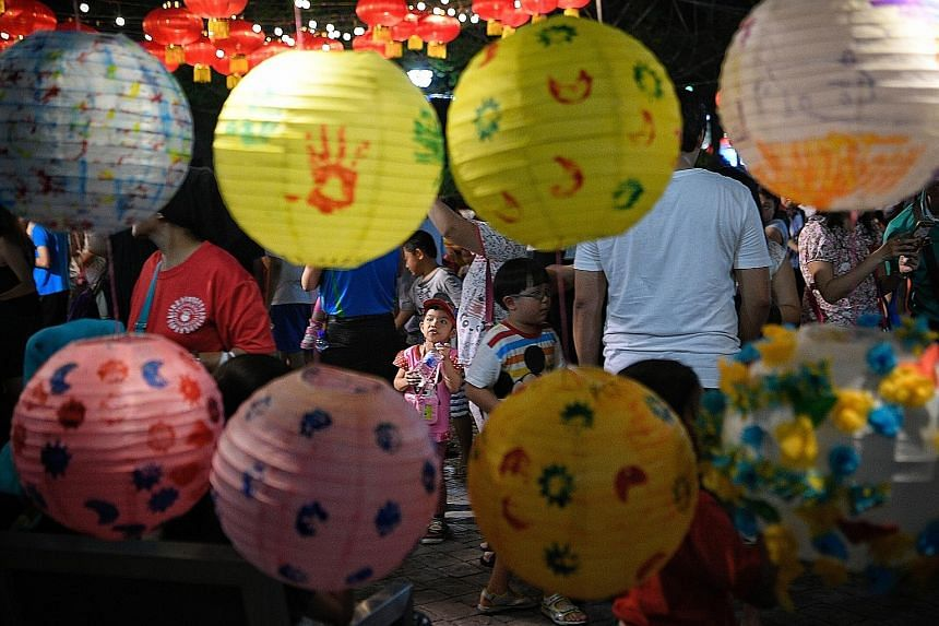 Lanterns decorated by pre-schoolers from PCF Sparkletots and My First Skool catch the eye of a young girl. The pre-schoolers had decorated 500 lanterns at a workshop, and their handiwork was displayed at a Mid-Autumn Festival celebration organised by