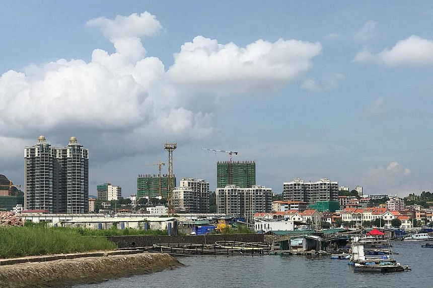 Fishermen's homes in Daya Bay, Huizhou, next to new buildings under development. The city's economic growth for the first half of the year was 7.5 per cent, while property investment shot up 23 per cent.