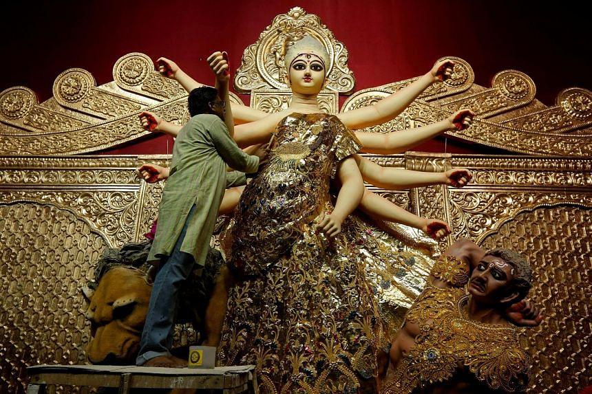 An artisan decorating a gold sari on an idol of Hindu goddess Durga, at a temporary platform called the pandal, ahead of the Durga Puja festival in Kolkata, India.
