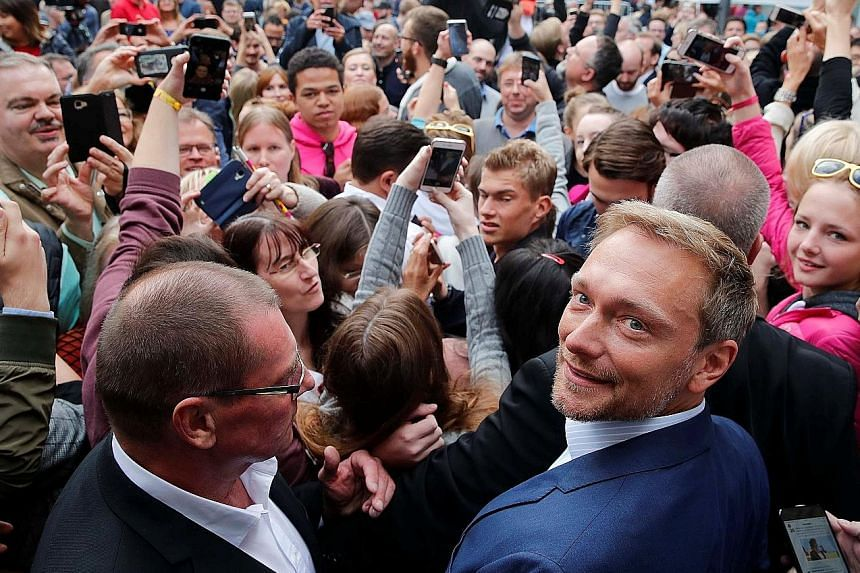 Free Democratic Party (FDP) leader Christian Lindner (in blue suit) with supporters eager to take a picture with him during a campaign rally in Dusseldorf, Germany, last Saturday. With Mr Lindner putting the spotlight back on the FDP, the party could