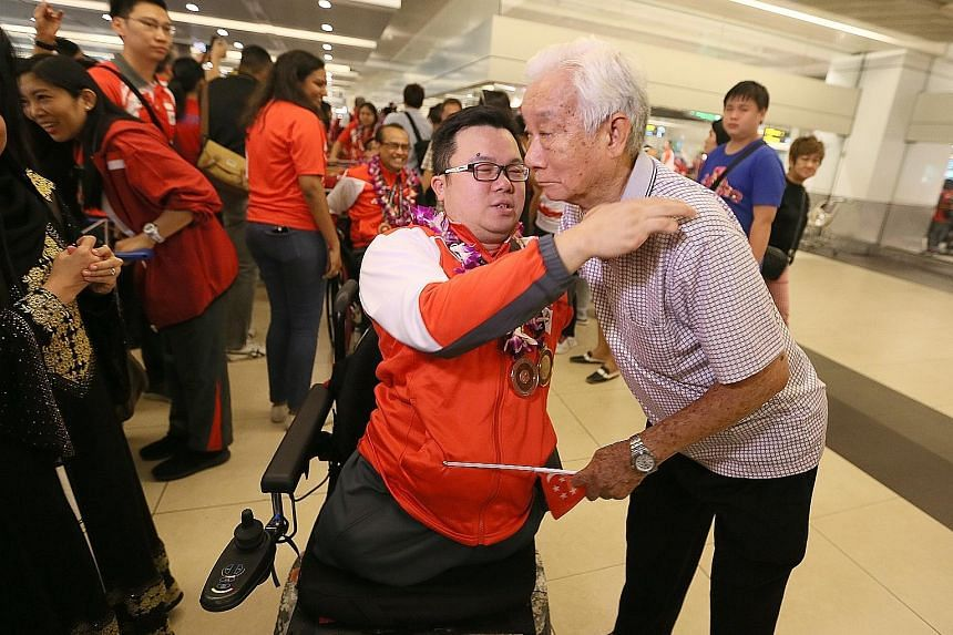 Jason Chee greeted by his father Chee Kwok Chor at Changi Airport as Singapore's Asean Para Games contingent returned from their record away medal haul at Kuala Lumpur. The contingent were treated to a rousing welcome at the arrival hall by a party t