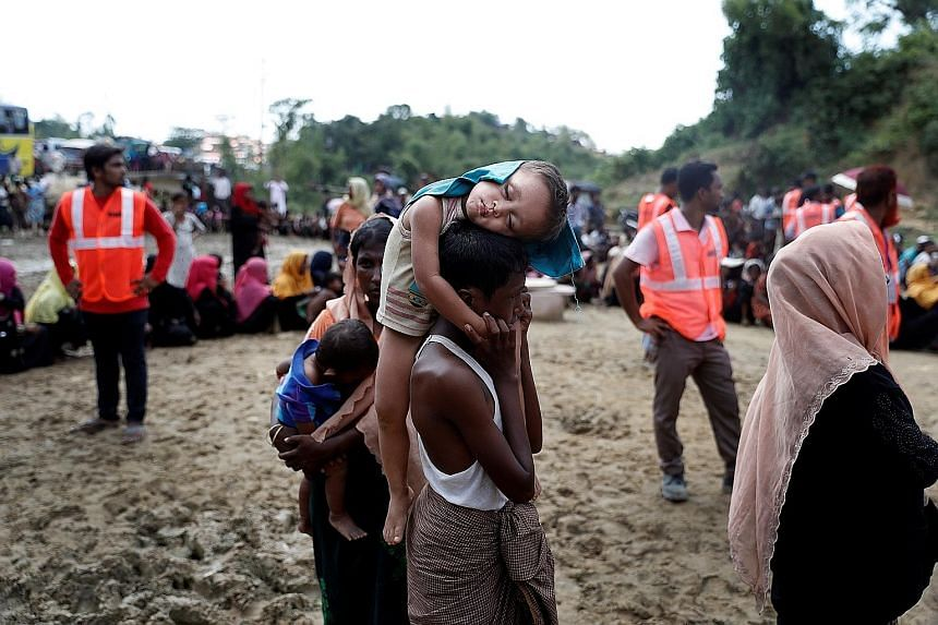A sleeping Rohingya refugee child in a queue for aid at a camp in Cox's Bazar, Bangladesh, last Friday. The Bangladesh government has yet to formulate a plan on how to address the humanitarian crisis without giving Myanmar an excuse to send all its R